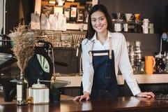 Azjatyckiej żeńskiej barista odzieży cajgowy fartuch umieszcza jej rękę na odpierającym b zdjęcie royalty free