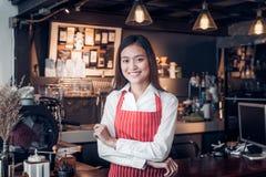 Azjatyckiej żeńskiej barista odzieży czerwony fartuch krzyżował jej ręki przy kontuarem fotografia stock