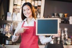 Azjatyckiej żeńskiej barista odzieży fartucha czerwony punkt przy pustym blackboard co obrazy royalty free