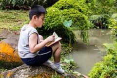 Azjatyckiej Chińskiej chłopiec czytelnicza książka w parku Zdjęcia Stock