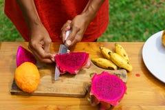 Azjatyckiej dziewczyny łupy smoka czerwona owoc, Indonezja, Bali Zdjęcie Stock