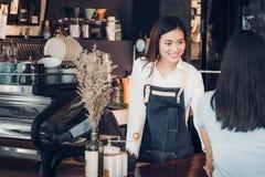 Azjatyckiej kobiety barista odzieży cajgowy fartuch trzyma filiżankę słuzyć zdjęcie royalty free
