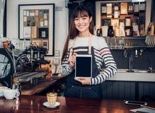 Azjatyckiej kobiety barista odzieży cajgowy fartuch trzyma pustego ekranu pastylkę obrazy stock