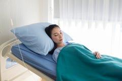 Azjatyckiej kobiety cierpliwy dosypianie na sickbed przy hotpital po bierze medycynę i krewni odwiedzają fotografia stock