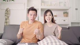 Azjatyckiej pary otuchy futbolowy dopasowanie przed telewizyjnym żywym pokojem w domu zbiory