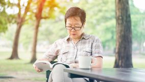 Azjatyckiej starszej kobiety czytelnicza książka pije kawę w pogodnym parku, g Obrazy Royalty Free