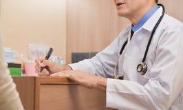 Azjatyckiej Starszej samiec Doktorski opowiadać z żeńskim pacjentem obrazy stock