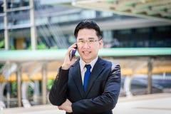Azjatykci biznesmen działanie na wiszącej ozdobie z szczęśliwym zdjęcie royalty free