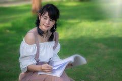 Azjatykci dziewczyny ` s obsiadanie w czytaniu i parku książka na fotografia royalty free