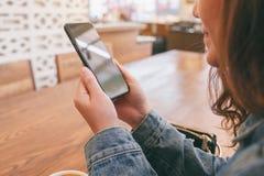 Azjatykci kobiety mienie, u?ywa? m?drze telefon i patrzej?cy w kawiarni obraz royalty free