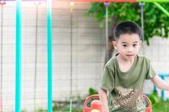 Azjatykcia chłopiec bawić się boisko na zamazanej drzewnej backgroud wiosce śmieszny Obrazy Royalty Free