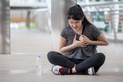 azjatykcia sprawności fizycznej młoda kobieta ćwiczy klatki piersiowej atak serca na ulicie w miastowym mieście lub bóle w trenin zdjęcie royalty free