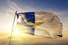 Azores flag textile cloth fabric waving on the top sunrise mist fog royalty free stock images