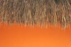 Azotea cubierta con paja y pared anaranjada Imagen de archivo libre de regalías