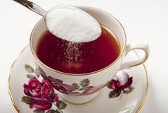 Azucare derramarse en taza de té Fotografía de archivo libre de regalías