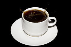 Azucare el cubo caído en una taza de café Foto de archivo libre de regalías