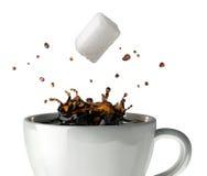 Azucare el cubo que cae y que salpica en una taza de café sólo. Opinión del primer. Imagenes de archivo
