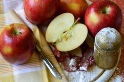 Azucare la coctelera, las manzanas y el cuchillo de la cáscara en la tajadera de madera Fotografía de archivo