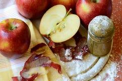 Azucare la coctelera, las manzanas y el cuchillo de la cáscara en la tajadera de madera Imagenes de archivo