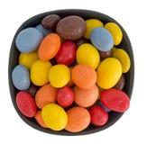 Azucare los cacahuetes revestidos del chocolate en el cuenco aislado sobre blanco Foto de archivo libre de regalías