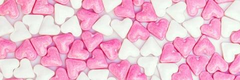 Azucare los corazones coloreados blancos y rosados, fondo del panorama Foto de archivo