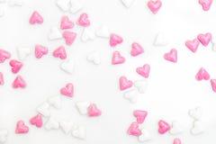 Azucare los corazones coloreados blancos y rosados, separándose en el backgrou blanco Fotografía de archivo libre de regalías