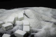 Azucare los cubos y el azúcar en una cuchara, pila del grano en fondo negro imagen de archivo libre de regalías