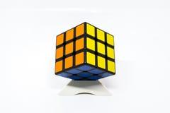 Azul acertado del amarillo anaranjado del cubo de Rubik con el soporte Foto de archivo libre de regalías