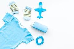 Azul ajustado para o menino recém-nascido O bodysuit do bebê, as peúgas, o brinquedo airplan e o pó na opinião superior do fundo  Imagens de Stock