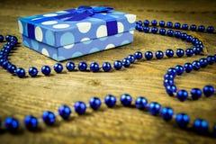 Azul bonito um presente com grânulos azuis em um fundo de madeira Foto de Stock