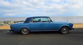 Azul clásico motor de Rolls Royce aparcamiento en la 'promenade' de la orilla del mar con la playa y el mar en fondo imagenes de archivo