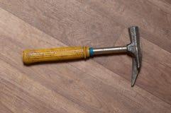 Azul con el martillo metálico amarillo en el piso laminado fotos de archivo libres de regalías
