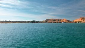 Azul da paisagem do verão, mar de turquesa, contra a costa amarela de montanhas do deserto Palmeiras, praia e hot?is para video estoque
