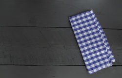 Azul de toalha de cozinha no fundo de madeira preto Imagens de Stock Royalty Free