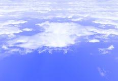 Azul del fondo del cielo con la opinión blanca de las nubes del top un avión Foto de archivo