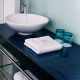 Azul del vidrio de agua de las toallas del contador del fregadero del cuarto de baño Imagen de archivo libre de regalías