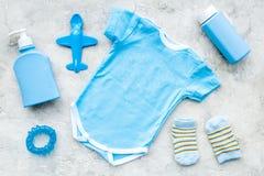 Azul fijado para el muchacho recién nacido Mono del bebé, calcetines, juguete airplan, jabón y polvo en la opinión superior del f Fotografía de archivo