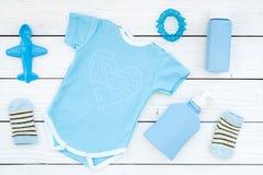 Azul fijado para el muchacho recién nacido Mono del bebé, calcetines, juguete airplan, oap y polvo en la opinión superior del fon Foto de archivo libre de regalías