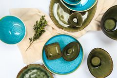 Azul hecho a mano rústico simple y loza verde contra la pared de madera blanca: plato, pila de cuencos Visi?n superior fotos de archivo