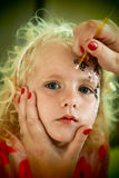Azul louro pequeno pintura eyed da cara da menina fotografia de stock royalty free
