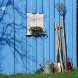 Azul vertido con los utensilios de jardinería Imagen de archivo