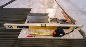 Azulejos e ferramentas para o tiler A instalação das telhas de assoalho Hom foto de stock royalty free