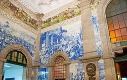 The azulejos in Porto. PORTO, PORTUGAL - APRIL 29, 2012: The interior of Sao Bento Railway Station with azulejo panel, depicting the historical events, on April Stock Photos