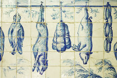 Azulejos representing food in old store of Lisbon Stock Photos