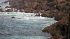 Azura rullar för havvågor på enormt vaggar på kustultrarapid arkivfilmer