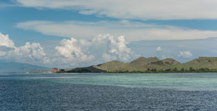 Azurblau schwemmte Ozeaneinhüllung am Fuß Felshügeln unter a an Stockbild