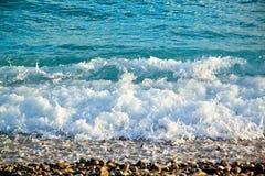 Azurblaue Meereswellen Klares blaues Wasser mit weißem Schaum Kiesel auf Th Lizenzfreie Stockbilder