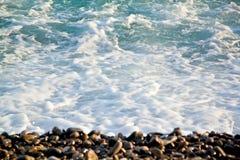 Azurblaue Meereswellen Klares blaues Wasser mit weißem Schaum Kiesel auf Th Lizenzfreies Stockfoto
