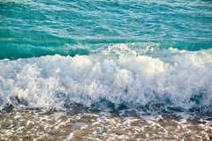 Azurblaue Meereswellen Klares blaues Wasser mit weißem Schaum Kiesel auf Th Stockbild