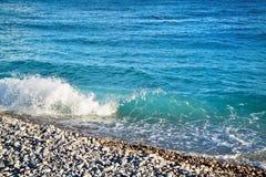Azurblaue Meereswellen Klares blaues Wasser mit weißem Schaum Kiesel auf Th Lizenzfreie Stockfotos